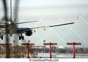 an airplane landing at barcelona airport shot with a tele zoom lens to focus close up on the runway