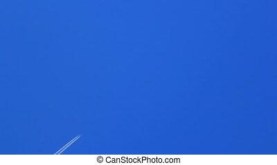 Airplane trail across blue sky