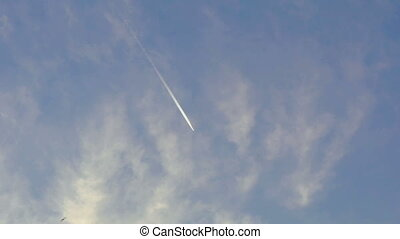 Airplane vapour trails across clear blue sky, birds flying....