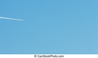 Airplane vapour trails across clear blue sky