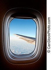 An airplane window with wing and cloudscape