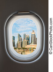 Airplane window and modern city skyline.