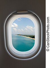 Airplane window from interior of aircraft and tropical beach.