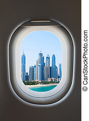 Airplane window from interior of aircraft with modern city view.