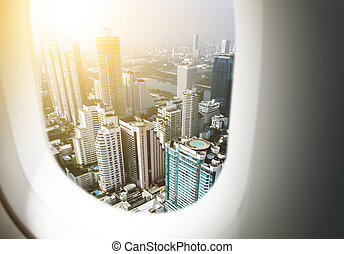Airplane window with city skyscraper and sun background