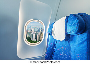 Airplane window with view on Hong Kong. Tourism and travel concept