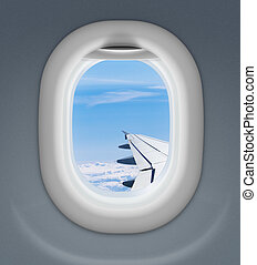 airplane window with wing and cloudy sky behind