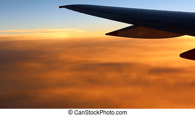 Airplane wing above orange clouds