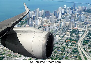airplane wing aircraft turbine flying on Miami downtown