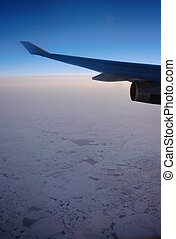 Airplane wing and sea ice on sunset, North pole