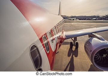 Airplane wing and turbine on airport background