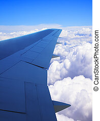 Airplane wing as viewed from window showing clouds and blue sky