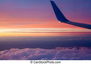 Airplane wing at sunset over the clouds. View from the window