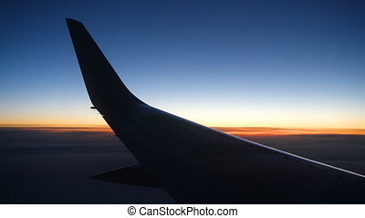 airplane wing at sunset time with clouds above