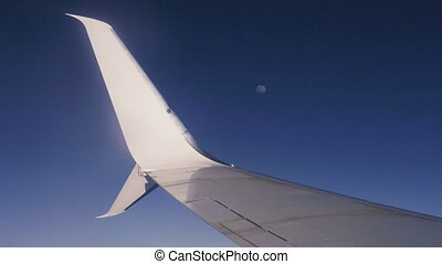 Airplane wing. From the airplane window you can see the wing of the aircraft and the moon