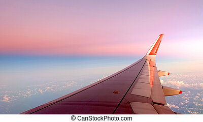 airplane wing with the sky in saturated gradient color from pink to light blue