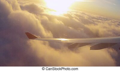 Airplane wing in flight over clouds