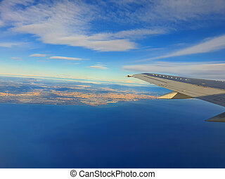 Airplane wing over sea