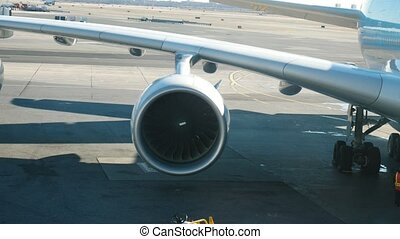 Airplane wing with engine - jet on airport - preparing for...