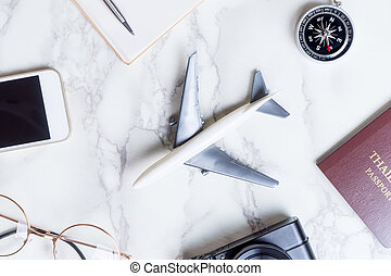 Airplane with travel accessories on marble surface