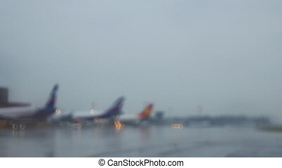 Airplanes at terminal sitting on a wet taxiway - Wide...