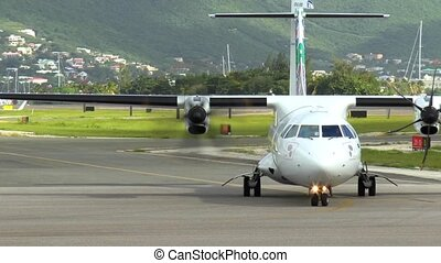 A twin engine airplane is seen on the tarmac after landing while other airplanes takeoff from the Caribbean Airport of Saint Martin.