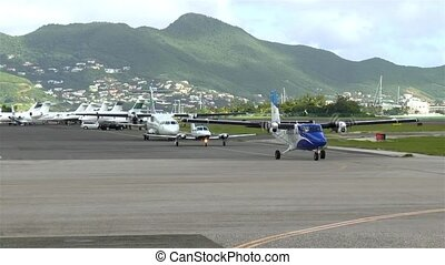 Airplanes line-up for takeoff at busy Caribbean airport.