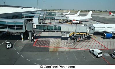 Airplanes sit parked at terminal of airport