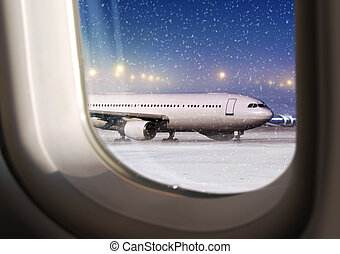 view through a plane window - airport and white aircraft at...