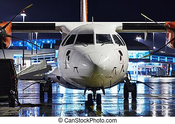 Airport at night - Airplane is waiting in rain on the...