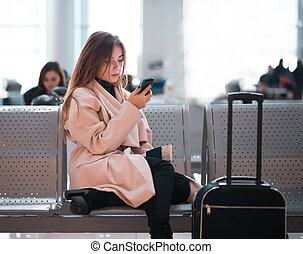 Airport business woman waiting in terminal.