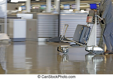 Airport cart - Motion image of a man pushing a cart in an...