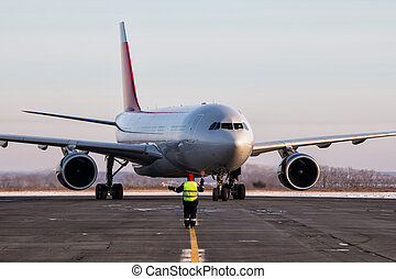 Airport ground crew meets passenger airplane that taxiing to the parking place in a cold winter weather
