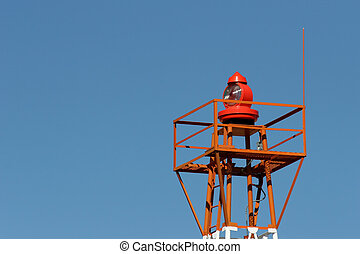 light beacon at a small airport against clear blue sky