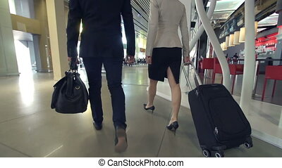 Airport Lounge - Camera following two people in formalwear...