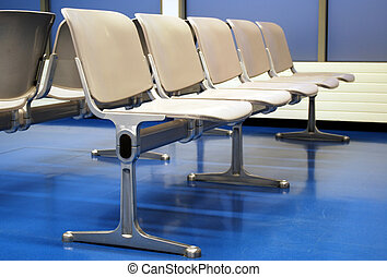 airport lounge with grey seats on blue floor