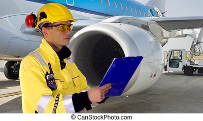 Airport mechanic - Person looking at his charts and...