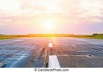 Airport runway airplanes with traces of rubber tires at dawn in the morning with sun glare.