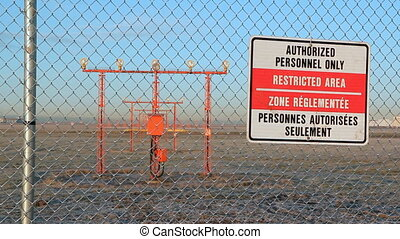 Authorized personnel only sign at perimeter of airport runway. Jet taking off. Vancouver, British Columbia, Canada.