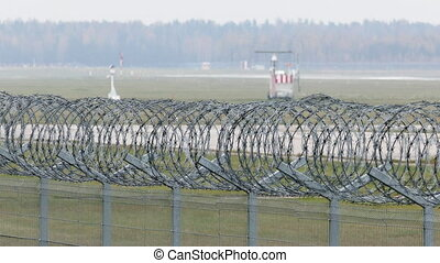 Airport runway behind security fence - Airport runway behind...