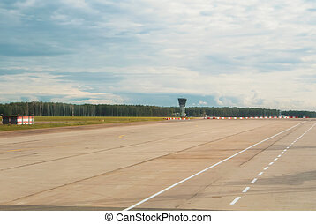 Airport runway with a forest at the background on cloudy day.