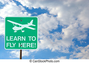 Airport Sign - Learn To Fly Here - with the cloudy sky as a background.