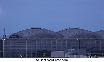 Airport terminal at night with plane taking off reflected in the windows, loopable