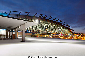 Airport terminal building and empty parking in the snow at night in Moscow