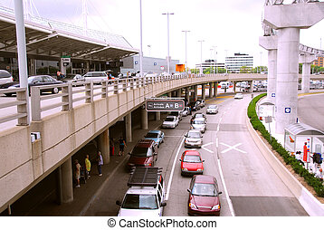 Travelers getting taxis at arrival area of airport