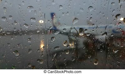 Airport through the window of the plane, it rains