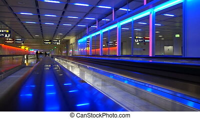 Airport travelers on moving walkway