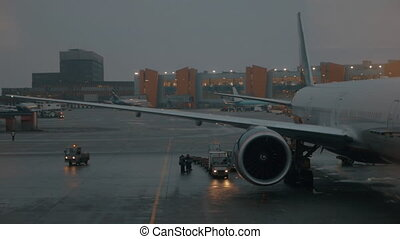 Airport view in the evening. Airplane and vehicles lights blinking