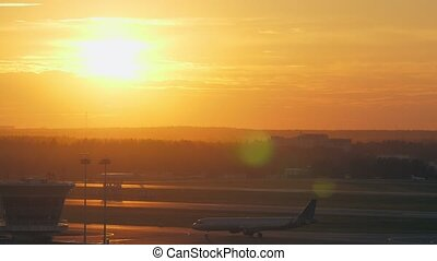 Airport view with moving plane at golden sunset - Slow...