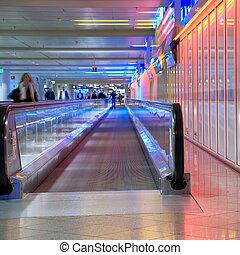 airport walkway pink - blurred paople on airport walkway